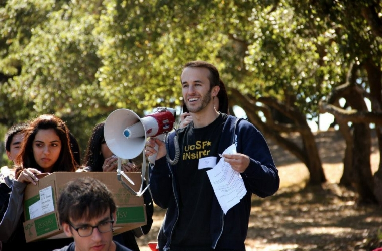 student smiling with a bullhorn, other students around