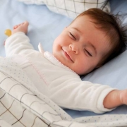 A baby sleeps with a smile on her face.