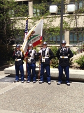 Four veterans in uniform, holding the California state flag, and US flag